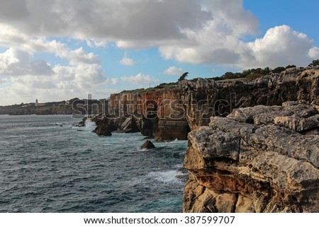 waves breaking on the cliffs in Cascais, Portugal