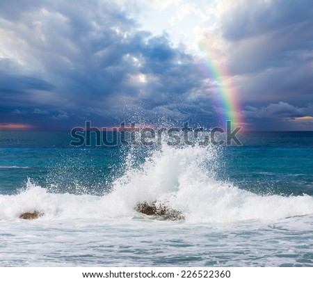 Waves breaking on the rocks against rainbow  - stock photo