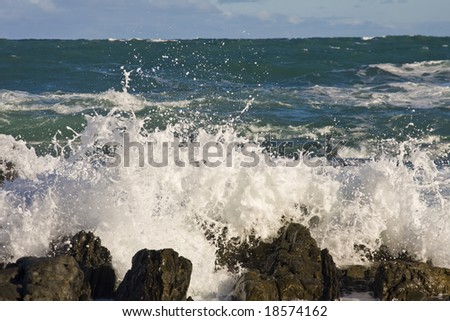 Waves breaking on the rocks on a beach in New Zealand - stock photo