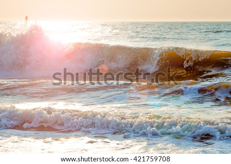 Waves breaking on the shore in The Netherlands. The sunset makes the photo color full image, with blue in the ocean gradient to the yellow sky and a powerfull sun flare just above the waves.