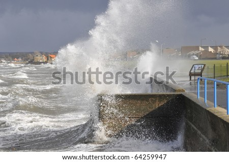 Waves breaking over sea wall 2 - stock photo