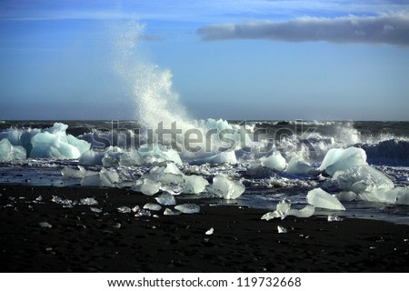 Waves breaking up the icebergs on the beach Iceland - stock photo