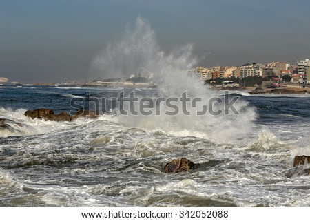 Waves breaking violently against rocks near the mouth of the Douro river, seeing in background all the coastal town of Porto in a stormy but sunny morning - stock photo