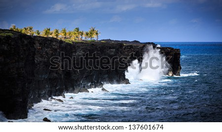 Waves crash along the black lava rock cliffs in the Hawaiian Volcanoes National Park.   This view is at the end of the Chain of Craters Road - stock photo