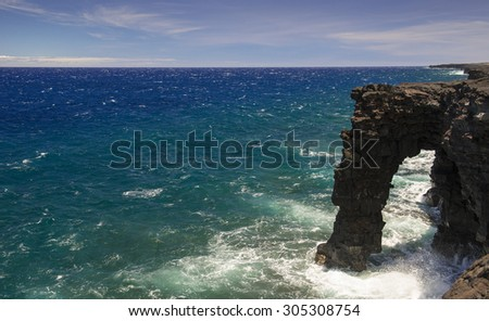Waves crash along the Holei Sea Arch in the Hawaiian Volcanoes National Park. This view is at the end of the Chain of Craters Road  - stock photo