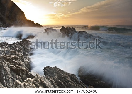 Waves crash over rocks as the sunrises over the ocean on South Africa's Otter Trail. - stock photo