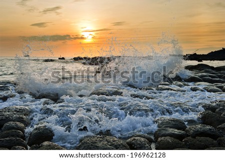 Waves crashing into the rocks with an orange sky behind it. - stock photo