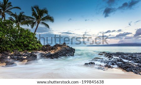 Waves crashing on the beach of Secret cove at dawn on Maui, Hawaii - stock photo