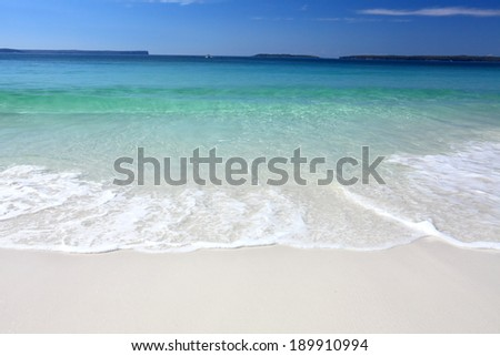 Waves crashing on the beach shore line on a beautiful sunny day - stock photo