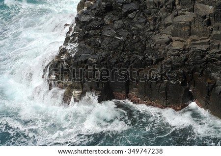 Waves crashing on volcanic cliffs. - stock photo