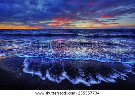 Waves crashing onto shore at dusk - stock photo