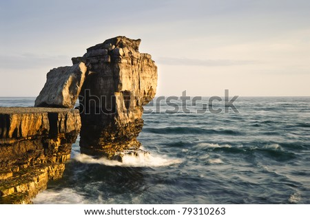 Waves crashing over rock formation cliffs at sunset with beautiful light on rock faces - stock photo