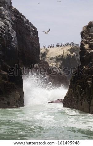 Waves crashing over the Palomino Islands, Peru, South America. - stock photo