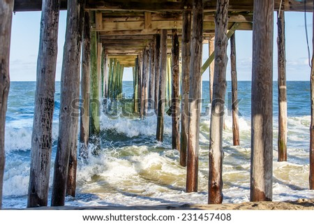 Waves crashing under the fishing pier  - stock photo