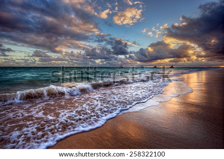Waves cresting onto a sandy beach with distant boats - stock photo