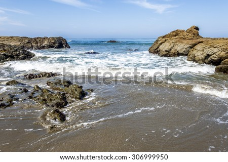 Waves crushing / breaking on a private / secret sandy / rocky beach making sea foam along the rugged Big Sur coastline, near Cambria, CA. on the California Central Coast. - stock photo