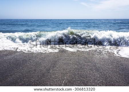 Waves crushing / breaking on a sandy beach making sea foam along the rugged Big Sur coastline, near Cambria, CA. on the California Central Coast. - stock photo