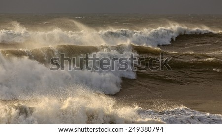 Waves during a winter sunset before rain. Shallow DOF. - stock photo
