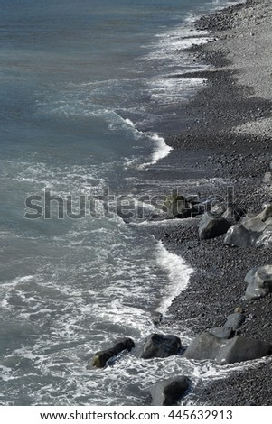Waves from Atlantic Ocean breading on beach of volcanic rock in Madeira, Portugal