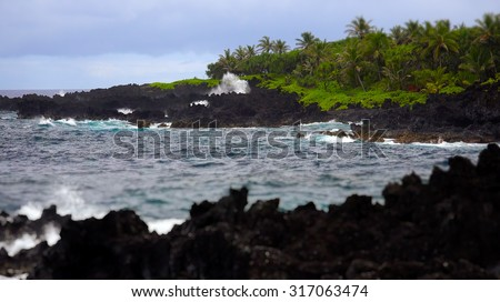 Waves from the pacific ocean break against the black volcanic rock shoreline of Maui - stock photo
