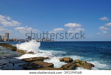 Waves hitting rocks next to The Malecon which is a broad esplanade, roadway and seawall which stretches for 8 km along the coast in Havana, Cuba - stock photo