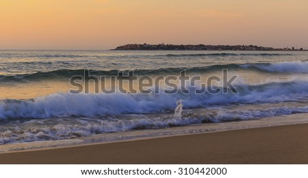 Waves in Sunny Beach on the background of the old town of Nessebar - stock photo