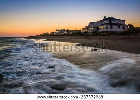 Waves in the Atlantic Ocean and beachfront homes at sunset, Edisto Beach, South Carolina. - stock photo