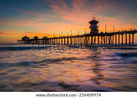 Waves in the Pacific Ocean and the pier at sunset, in Huntington Beach, California. - stock photo