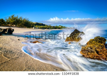Waves lapping on the sandy beach at Boucan Canot on Reunion Island in the Indian Ocean. - stock photo