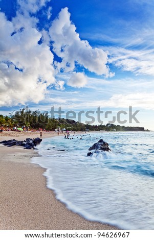 Waves lapping on the sandy beach at Boucan Canot on Reunion Island in the Indian Ocean.