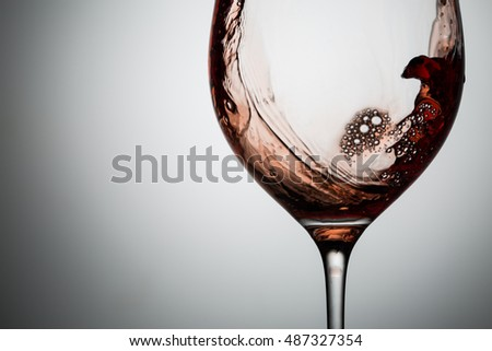 Waves of red wine and bubbles on the side of glass