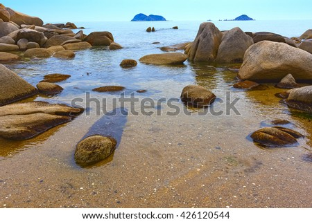 Waves of the Pacific Ocean on the rocks. Sand on the seashore. Wild beach - stock photo