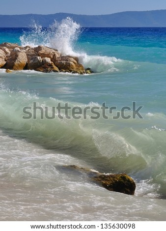 Waves on beautiful beach with stones in Podgora, Croatia