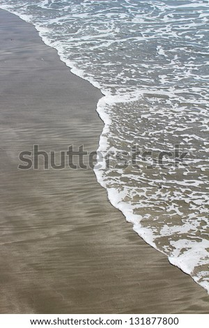 Waves on Sand Beach, Vertical - stock photo