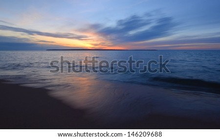 Waves on the Beach and Sunset Over Sand Island of the Apostle Islands in Wisconsin - stock photo
