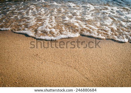 Waves on the beach with copy-space on the sand - stock photo