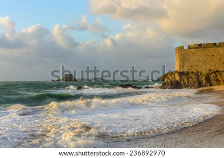 Waves on windy weather in Saint Malo with a little fortress in the distance, Fort du Petit Be, St Malo, France  - stock photo