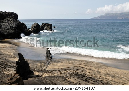 Waves roll into a mixed color sand beach on the islet of Djeu in Cabo Verde