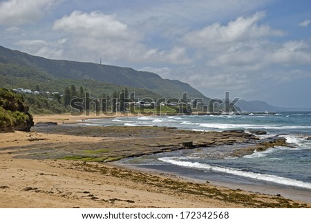 waves roll into shore at a resort beach - stock photo