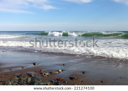 Waves rolling onto a sandy beach in summer - stock photo