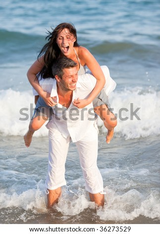Waves running laughing piggy-back sea water lover couple enjoying summertime in ocean holding together watersport - stock photo
