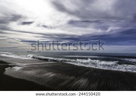 Waves, sand, blue sky and sea, on Moonstone Beach, California Central Coast, near Cambria CA. - stock photo