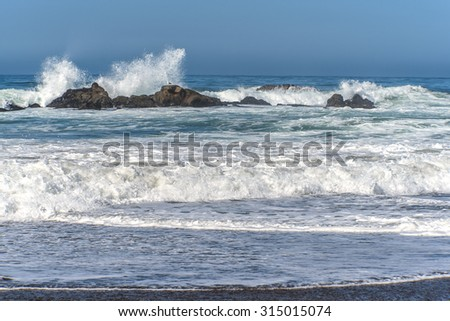 Waves splashing / crashing on huge rocks, off shore, along a rocky coastline, fog & low clouds cover the horizon line, traveling the Big Sur Highway (Highway 1), on the California Central Coast. - stock photo