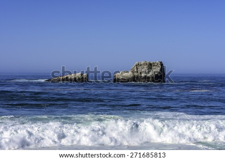 Waves splashing on huge rocks, off shore, along a rocky beach, close to the Big Sur Highway (California State Highway 1), on the California Central Coast, near Cambria CA.