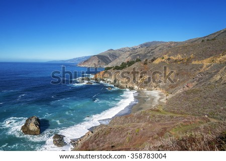 Waves splashing on huge rocks, off shore, along a rocky coastline, fog & cloud covered mountain tops, China Basin Beach, traveling the Big Sur Highway (Highway 1), on the California Central Coast. - stock photo