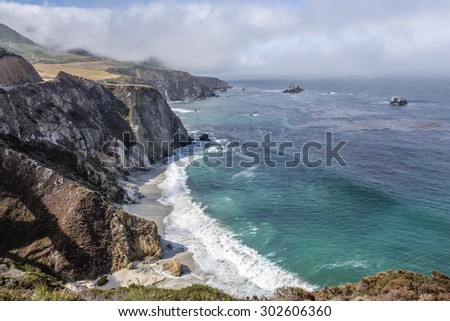 Waves splashing on huge rocks, off shore, along a rocky coastline,fog & cloud covered mountain tops, bridge, traveling the Big Sur Highway (Highway 1), on the California Central Coast. - stock photo