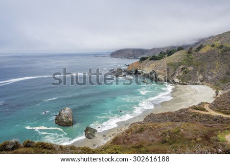 Waves splashing on huge rocks, off shore, along a rocky coastline,fog & cloud covered mountain tops, bixby bridge, traveling the Big Sur Highway (Highway 1), on the California Central Coast. - stock photo