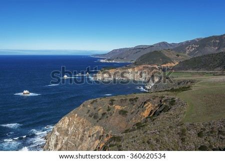 Waves splashing on huge rocks, off shore, in aquamarine seas, along a rocky coastline, the Bixby Bridge in the distance, traveling the Big Sur Highway (Highway 1), on the California Central Coast. - stock photo