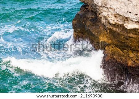 Waves splashing on rock - stock photo