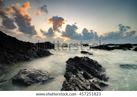 waves splashing on the unique rocks formation over beautiful sunrise background.soft focus image due to long exposure